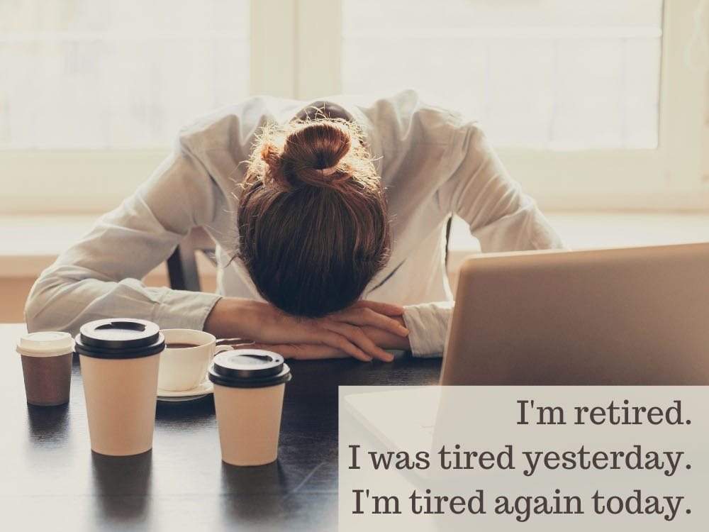 Woman slumped at desk surrounded by coffee and laptop - tired